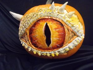 Pumpkin carved and decorate to look like a dragon's eye, using pumpkin seed scales, food coloring, and la doll modeling clay